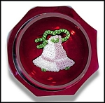 "Pink and white bells made of tiny stardust canes are tied together by a green ribbon and rest on a deep red ground on this 8+1 faceted paperweight.  LE of 318.  Diameter: 3""."
