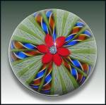 A one-of-a-kind Perthshire crown paperweight with a central red lampwork flower with a complex center cane, and radiating reddish-orange, blue and white twists alternating with white latticino and so...