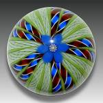 A one-of-a-kind Perthshire crown paperweight with a central blue lampwork flower with a complex center cane, and radiating deep red, blue and  white twists alternating with white latticino and solid g...