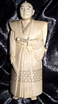 Click here to enlarge image and see more about item 103108002: Ivory figurine of robed oriental man with sword.