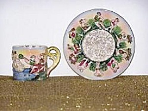 O.J. CUP & SAUCER W/RAISED FIGURES (Image1)