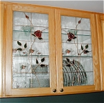 Roses on a clear textured background provide a touch of elegance to these kitchen cabinets.