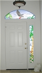 The sidelight in this entryway reminds the owners of their times in Hawaii, with blooming plumeria and hibiscus flowers, and their sailboat setting out to sea.  Sinbad, their African Grey, flies overhead in the transom window.