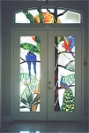 These colorful tropical birds create the perfect entryway for this home on Macaw Lane.  A pair of Hyacinth Macaws, a Scarlet Macaw and a Peacock all rest on a tree underneath a glowing sun.  This stained glass entryway was a birthday present from wife to husband.  It was kept a secret until installation day, and he didn't get to see his surprise until installation was complete.  The look on his face said it all.  He was ecstatic!  And she was tickled pink that he was so happy with his surprise!
