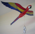 "This gorgeous hanging scarlet macaw will add a colorful tropical flare to any room.  A light pull and release of the flower makes the macaw ""fly"" for several seconds.  This bird is big. The wingspan is 26 inches when fully extended. The body measures 19-1/2 inches from beak to the end of the tail feathers, and the overall height is 33 inches from the hanging loop to the bottom of the flower."