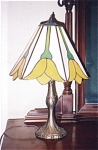 This panel lamp has six sides, created with a white whispy opaque background glass, and beautiful bright yellow opaque glass tulips. The shade measures 9 inches tall and 11 inches in diameter. The overall height of the lamp, including the heavy cast base, is 17 inches.