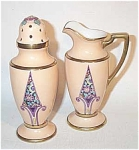 This Noritake Art Deco muffineer set is the standard shape but with a spectacular design of a black background chevron or spear shape coming up from the lower part of each piece. Highly enameled abstract blossoms fill the purple outlined space. The body of each piece is a salmon pink color which is unusual for Noritake. Gold trim on rims and shoulder of each piece. Excellent condition. Red wreath mark.