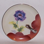 Noritake 5 inch Deco  purple flower airbrush server with a lovely handpainted purple/blue flower rising out from a deep orange/rust side border. Shown in Spain A-Z p. 212, plate P.55. Silver handle a little worn. Red mark. A really pretty little Noritake serving piece. 
