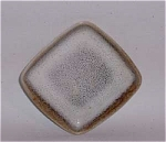 Produced by Vermont Mid-Century studio potter Stanley Ballard, a student of Glidden Parker at Alfred University in the 1940s who worked in the Burlington area,  this  3 5/8 inch square dish is a very early studio piece as it carries no shape number and was most likely hand formed. It has a very heavily mottled white glaze over a chocolate brown underglaze and sloping sides. A great example of Ballard's glaze and early shape. It is in excellent condition.