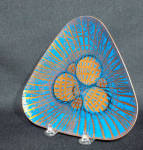 Annemarie Davidson (1920-2012) learned her enameling craft first from the great Doris Hall (1907-2001) in Cambridge, MA  in 1957. In California she continued her studies with Curtis Tann.  Her combination of geometric and organic form in her designs culminated in her most celebrated abstract designs, her Jewel line which features pieces of glass used to create free-form organic shapes which she calls Jewels. She also uses a sgraffito technique, incising straight lines from the center of her plate with the sharp point of a dart.   This 6 1/4 inch plate, most likely from the 1961-1962 time period,  is unusual for its form, triangular.  This plate features 3 large yellow jewels and 3 smaller yellow jewels. The underlying copper color can be seen near the edges. A prominent Palm Springs CA dealer James Elliot-Bishop on his website has named this pattern as Grooveline.  The back of the plate is signed with her charcteristic AD interwined intiails and her paper black line label which reads Annemarie Davidson handcrafted enamels Sierra Madre California.  Every piece was handcrafted by her alone, from start to finish. Excellent condition.   The work of Annemarie Davidson was included in the seminal exhibit titled Painting with Fire which opened in Jan 2007 at the Long Beach Museum of Art. She was one of 30 enamelists included with a one page entry on her life and work. Her page is page 266 of the catalogue.