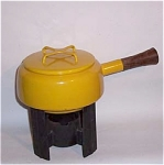 This funky and wonderful yellow fondue covered pan was produced by Dansk in France and is so marked on the bottom of the black iron base and on the bottom of the yellow pan.  The stands is 4 1/2 inches tall and is heavy. The center of the stand is where the sterno container would rest. It is missing the handled lid but I am sure that could be found from a vintage Dansk specialist or perhaps online. 