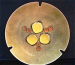 Annemarie Davidson learned her enameling craft first from the great Doris Hall (1907-2001) in Cambridge, MA  in 1957. In California she continued her studies with Curtis Tann.  Her combination of geometric and organic form in her designs culminated in her most celebrated abstract designs, her Jewel line which features pieces of glass used to create free-form organic shapes which she calls Jewels. She also uses a sgraffito technique, incising straight lines from the center of her plate with the sharp point of a dart.  