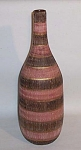 This Raymor Bitossi Seta bottle shaped vase stands 15 inches tall. It is covered with both vertically incised lines and indentations horizontally in  the body of the piece. The piece has been painted in black, deep pink, and gold done in horizontal bands. It is simply a stunning piece of Eames era Midcentury ceramic art. The bottom is signed V222/43 and the word Italy in bold black letters. I would guess that the piece is Bitossi by the way the IT of Italy is written. It is in excellent shape. It would great on a Paul McCobb piece or even a Noguchi table.