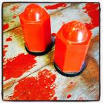 Deco red plastic hexagonal bullet shakers with black bases which can be unscrewed to refill. They stand 2 inches tall. A great Art Deco combination of form and function.