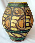 This vase stands 7 inches tall and is 3 inches wide at the mouth. It is done in the Brutalist manner of the late 1950s-early 1970s. The surface of the terra cotta vase is covered with a chocolate base glaze over which a spattered layer of glazed was added to add texture over which the colors have been applied, with thick black lines outlining the colored sections. A bland band is at the bottom and the top Above the bottom black band there is a band of black diagonal lines. A very abstract bird with orange eye and tail circles the vase. The body of the bird is done in yellow with black lines separating the yellow sections.  The same horizontal aquamarine color band outlined in black can be seen in three different places on the vase. 