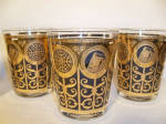 This set of 15 oz. Rocks glasses features two panels each depicting three abstract flower forms whose flowers feature a classical design and in the middle the Rock of Gibraltar.  The decoration is 24 karat gold on black.  Two designers, Fred Press and Georges Briard designed many such lines, though these are not signed in any way.  Buy them! Fill them with your favorite retro drink and the party is on.  Go green! Save resources and purchase a piece of America's past. Sturdy, dependable, they are ready for your bar or dining room today.