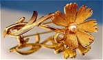<b>Warm gold-tone color. Faux pearl center. Serrated petal edges for an authentic look. Fluid motion of stem and leaves.