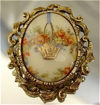 <b>A loveely floral arrangement burst from this golden hanging basket, held up with a blue ribbon.  The antiqued golden scroll-work frame gives this brooch its finishing touch. 