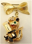 <b>Simply delightful goldtone scent holding brooch.  Golden bow with an enamel black and white skunk holding a vial for your favorite scent.  The reverse side has an embossed word STINKY in red enamel.  Stinky has an emerald rhinestone eye.  His vial is a screw top.  When you wear Stinky, you will always have your favorite scent close at hand!  There is some emamel paint wear, especially on the back side.