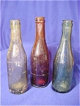 All three bottles have mold lines to the top of lip.  The dark green bottle has no makers marks but indented on the bottom.  The light green bottle is embossed on bottom with: J L & C. L. C 1900.  The brown bottle is embossed on bottom: S. B. & C. Co  4.  They range in size from 7 3/4 in. to 8 in. tall.  Each bottle has various bubbles in the glass.  The brown one has some paint spatters on it.  These bottles need to be cleaned.