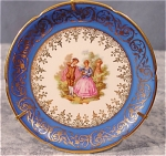 <b>Blue outer rim with heavy gold trimmings.  Center of plate has courtship scene. Elongated scallop edging. 