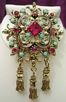 <b>This is a breath-taking brooch with deep pink, lime green rhinestones and faux turquoise all set in an antique gold color setting. Then finally, accented with three dropped golden tassels. 