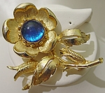 <b>Stunning blue cabochon takes center stage in this golden flower.    Stamped:  Exquisite and Reg.  Open back. Double barrel closure.