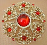 Click here to enlarge image and see more about item 401: Sarah Coventry Round Openwork Brooch with Red Cabochons