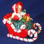 Click here to enlarge image and see more about item 14249: Lefton Christmas Shopper Girl in Candy Cane Sleigh