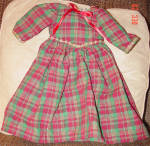 This is a skillfully handmade red and green plaid cotton dress has gold braid and red ribbon trim, and it fits 18 inch dolls including American Girls, Magic Attic Club, Large Tonner Ann Estelle, Alexander Dear America, and other similar size dolls. This dress has a long skirt and long sleeves. The green in the material sparkles. Gold braid trim decorates the waist, neckline, and long sleeves. This dress is perfect for dressing a doll for Christmas. It has a velcro closing so it is easy to remove. Marilyn Taylor made this one of a kind doll dress by hand. New, mint condition. Expand listing to view both photographs.
