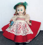8 inch Madame Alexander Swiss girl doll, No. 394 has a Maggie face, blonde wig styled in braids with red ribbons under a green Tyrolean hat with red ribbon, and moving green eyes. She is a bending knee walking doll from approximately 1966. The walking mechanism works and her head moves from side to side. She has lighter coloring. She has her small original hang tag, but no box. Her clothes are all original. Besides her hat she is also wearing her Tyrolean dress with a full red felt skirt and white bodice, white lace apron, white petticoat with red rickrack edging, white pantaloons trimmed with red bows, white socks, and original black slip-on cloth shoes with gold buttons. She is holding a bouquet of flowers. This adorable doll is in excellent condition. Her outfit is complete, but the elastic is slightly stretched, though the clothes still stay up. The white white has turned ivory with age. Expand listing to view all photographs.