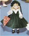Madame Alexander 1987 14 inch Bellows Anne  with Parasol doll. She is a vinyl doll with a  Mary Ann sculpt face, rooted blonde hair in a flip style, and moving blue eyes. She is dressed in a dark green velvet jumper with white long sleeved blouse, a dark green duster cap, and dark green shoes. Includes a red floral print parasol. This old stock doll is mint-in-the-box with booklet.