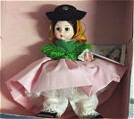 Madame Alexander 8 inch Portugal No. 585, 1982-1984 hard plastic doll has bisque-type coloring, a Wendy face, a brunette wig, and moving brown eyes. This Portuguese doll is wearing  a pink skirt, a white long sleeve blouse, a green shawl, black hat and deep yellow scarf. This discontinued doll has her box and tag; the flaws are that the pink skirt has faded as pictured and stretched elastic at the pantaloons and hat, so this doll's price is reduced.
