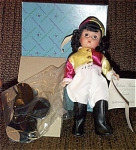 1995 Madame Alexander 8 inch National Velvet doll with Wendy face, represents the young Elizabeth Taylor as she was when she starred in this classic movie. She has a dark brunette wig, blue moving eyes, and a  beauty spot. She is dressed in a colorful white, yellow, rose riding outfit, and has a saddle as in the movie. Mint-in-box old stock with tag.