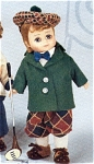 1998 Madame Alexander 8 inch Golf Boy Doll with a Maggie face, has a red wig, and moving blue eyes. This little golfing boy is dressed in brown and tan plaid ankle-length pants, a white shirt, a blue bow tie, a green jacket, a brown and tan plaid tam-type hat with a brown pompom, white socks, and tan shoes. He is holding his golf club. This boy doll looks like he stepped out of the 1920s. Mint-in-the-Box Old Stock with Tag, directly from Alexander Doll Co.