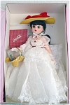 Madame Alexander 1999 16 inch Nostalgia Coca-Cola doll, is a Coco doll with brunette hair and moving blue eyes. Her costume is like the lady in the old Coca Cola logo. It consists of a long white lace dress, large straw hat with red ribbon. Her accessories include a picnic basket with a Coca Cola miniature bottle and a red and white checked cloth that says 'Coca Cola'. This doll was licensed by Coca Cola. New old stock that is mint-in-the-box with tag.