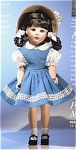 1999 Madame Alexander 15 inch all-bisque reproduction of the classic Margaret Ann doll, has a wig styled in brunette looped braids with white ribbons, and blue inset eyes. She is wearing a replica of the outfit of the composition doll of the 1940s. It includes a blue cotton pinafore with white lace trim, voile petticoat white blouse with puffed sleeves, natural straw bonnet-type hat with white flowers. Retired doll is new and mint-in-the-box with paperwork.