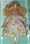 Madame Alexander 1999-2000 14 inch Meagan, in John Lennon-inspired clothes. This blonde vinyl play doll has short pale blonde hair with bangs and a print headband with bow that matches her printed dress, and blue moving eyes. She is wearing a front-buttoning dress with a print of Carter's friends in pastel colors on a white background, and white shoes. The print of her dress is of bird, cat, child, dog, and word friends. Discontinued doll is new and mint in her window box. Expand listing tot view both photographs.