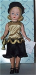 Madame Alexander 1999 Fall limited edition 1920 Golden Girl doll has a 10 inch hard plastic Cissette fashion doll body with high heeled feet. This doll's pale blonde wig is in a flip style, and she has blue moving eyes. She is wearing a flapper-era dress with a gold satin bodice with black beads and gold chain trim at neck and waist line with gold loops at waist, a black pleated skirt, and a black straw hat. Her accessories include a tiny gold purse, stockings, and black high heel shoes. New and mint-in-the-box with tag old stock.