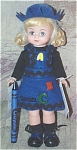 Madame Alexander 2000 8 inch hard plastic Blue Crayola Doll, No. 17840, has a Maggie face, blonde curly double ponytails, and moving blue eyes. She is wearing a black leotard, a blue felt jumper that says Crayola with A, B, C buttons, a blue felt hat, and black lacing shoes. She is holding a blue crayon. Mint-in-the-box old stock with tag.