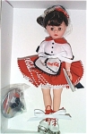 Madame Alexander 2000 Coca Cola Carhop Doll, No. 17401, has a Cissette face, brunette wig styled in a ponytail and moving brown eyes. This hard plastic doll is 10 inches tall. Her red and white Coca Cola waitress uniform consists of a white with red trim blouse and full red mini-skirt that says 'Coca Cola' in white and a white with red and black trim apron that advertises 'Coca Cola'. She fills her orders while riding on white skates with red ties, and her hat is like a Coca Cola bottle cap. Miniature Coca Cola bottles on a tray that says 'Coca Cola' are included. This is a licensed Coca Cola collectible. Old stock doll is new and mint-in-the-box with tag.