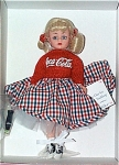 Madame Alexander 2000 Time Out for Coca-Cola Sockhop, No. 26225, is a 10 inch hard plastic doll with a Cissette face and body. Her blonde wig is styled in double ponytails tied with red ribbon, and she has blue moving eyes. Her 1950s-era ensemble includes a red sweater that says 'Coca Cola' and a red, white, and blue box print full skirt with petticoat underneath, and black and white saddle oxford shoes and white socks similar to 1950s fashions. A little Coca Cola bottle is included. This is a licensed Coca Cola collectible.  Mint-in-the-box with tag old stock in new condition.