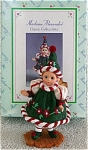 1999 Madame Alexander 6 inch resin Santa's Little Helper Figurine representing the  8 inch Wendy little Elf Doll which was introduced in 1998. This figurine depicts a popular Madame Alexander Wendy doll with long red braids, green eyes, and pointed ears. She is wearing a green felt dress with red and white striped hem and collar, white puff sleeves with white stripes, and poinsettia motifs. Her pointed elf hat is green with red and white stripe brim, poinsettia motifs, and red pompom, and she is wearing pointed green shoes with red pompom toes and red and white striped stockings. Figurine is standing on a floor-type base. Llimited edition figurine is new, mint-in-the-box old stock, and includes its certificate and packing box.