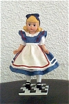 1999 Alice figurine by Alexander Doll Company is a detailed bisque resin figurine represents the 1995 blonde Alice in Wonderland doll. She is wearing her classic blue dress and white apron with red piping. This blonde Alice figurine is 6 inches tall and stands on a game board. She is one of several figurines of dolls in the first resin figurine series done by Madame Alexander. This discontinued figurine is new, mint-in-the-box old stock, and includes its packing box and a certificate.