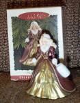 1996 Hallmark Happy Holiday Barbie Keepsake Ornament, No. 2761, is an ornament version of the 1996 blonde Happy Holiday Barbie doll. She is wearing a long burgundy with gold accents formal evening gown, a white muff and a white decorated hat. Lower priced insured First Class Mail shipping is available by request in the comments section of the order form, and the rate will be adjusted. New, and mint-in-the-box old stock.