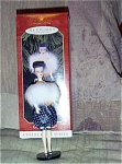 1998 Hallmark Gay Parisienne Classic Barbie Ornament depicts a classic brunette Barbie doll. Her ensemble includes a dark blue bubble dress and a white fur boa, like the late 1950s-early 60s classic doll fashion. Retired Christmas ornament is new and mint-in-the-box.