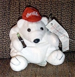 Small Coca Cola Polar Bear Bean Bag Plush, No. 0111, is wearing a Red Baseball with Coca Cola Logo. He is holding a bottle of Coca Cola in one paw. His tag is shaped like a Coca Cola bottle cap. A Coca Cola label is attached to his body. He is 7 inches in height. This retired bean bag is from the first set of Coca Cola bean bags in 1997. This bean bag plush is in new old stock in mint condition.