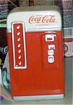 Coca Cola Vending Machine Ceramic Figurine  was made by Enesco from 1993-1994. It is approximately 5 inches tall. The figure is colored red and white as the older Coca Cola machines were. This figure is in new, mint-in-the-box condition.