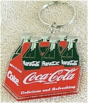 Enesco heavy plastic key chain of a vintage Coca Cola bottle six-pack. This key chain is new and mint. It was produced in approximately 1993. On orders of 1 to 6 Coca Cola key chains and/or magnets, lower priced insured first class mail or first class mail international is available, if the request is put in the comments section of the order form; the total will be adjusted.