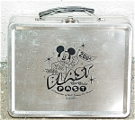 2004 Disney Blast to the Past Lunch box. This pre-owned silver-colored metal lunch box has a black drawing of Mickey Mouse who is holding a 2004 flag and dressed in an 'M' shirt. The printing on the lunch box says: 'A Celebration of Walt Disney Art Classics.' This lunch box would also could be used as a trinket box. It is a rectangular shape with a good intact black plastic handle. Very good condition; except for a few small faint scratches.